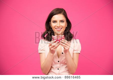 Happy young woman eating donut and looking at camera over pink background