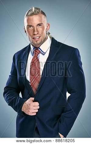 Portrait of an attractive young businessman wearing black suit. Blonde hair
