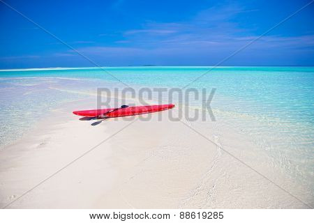 Red surfboard on white sandy beach with turquoise water
