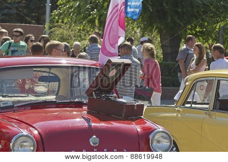 Old gramophone stands on the hood of Moskvitch Mzma 407t