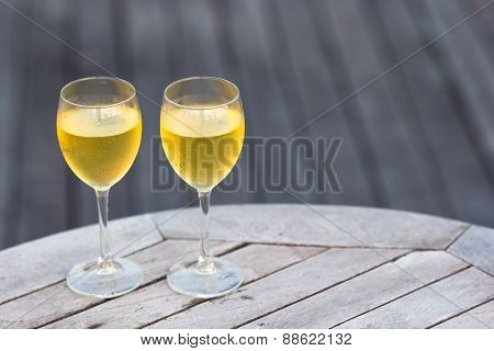 Two glasses of tasty white wine at sunset on wooden table