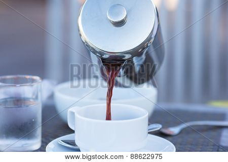 Closeup of teapot and coffee in a white cup