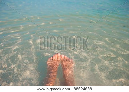 Female feet on white sandy beach and clear water