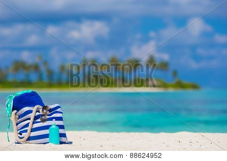 Stripe bag, blue towel, sunglasses, sunscreen bottle and swimsuit background turquoise water and gre