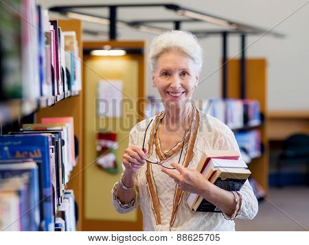 Elderly lady standing next to book shelves in library