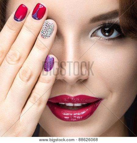 Beautiful girl with a bright evening make-up and red manicure with rhinestones. Nail design