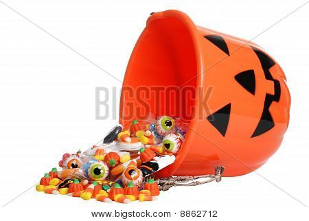 child halloween pumpkin bucket spilling candy