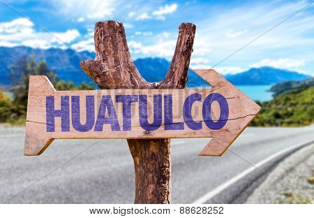 Huatulco wooden sign with road background