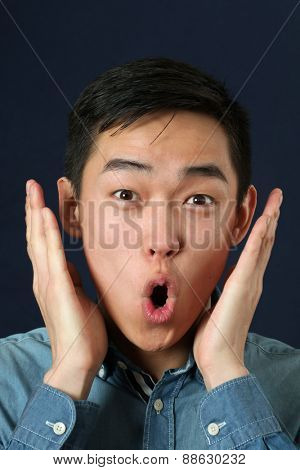 Surprised young Asian man looking at camera
