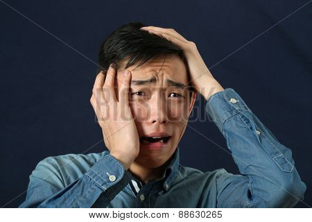 Disappointed young Asian man crying and looking sideways