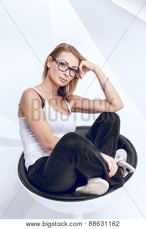 Young creative woman sitting on the modern chair on white background