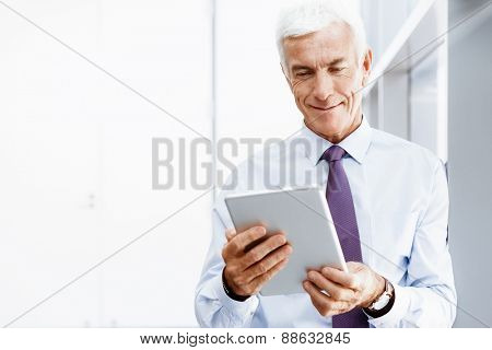 Businessman standing with tablet smiling at camera