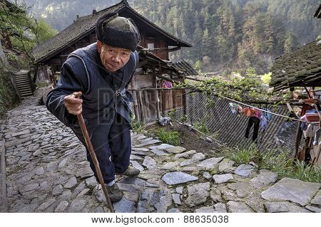 Aged Asian Walks Along Stone Road, Laying On His Stick.