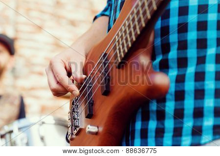 A street musician playing his guitar close up