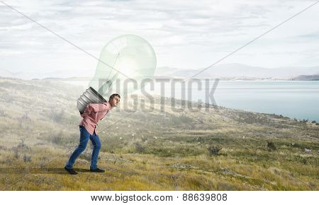 Young guy carrying light bulb on his back