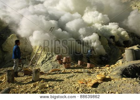 KAWAH IJEN, INDONESIA - AUGUST 9, 2011: Miner collects sulphur in the fumes of toxic volcanic gas at the sulphur mines in the crater of the active volcano of Kawah Ijen, East Java, Indonesia.