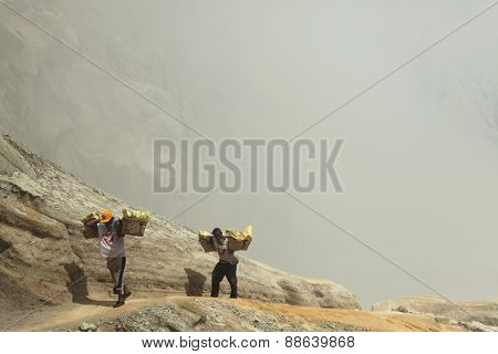 KAWAH IJEN, INDONESIA - AUGUST 8, 2011: Miners carry baskets with sulphur in fumes of toxic volcanic gas from the sulphur mines in the crater of the active volcano of Kawah Ijen, East Java, Indonesia.
