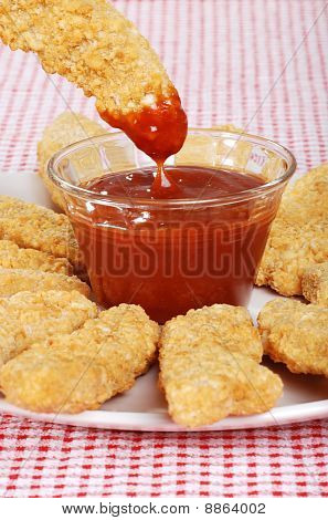 dipping chicken finger in BBQ sauce