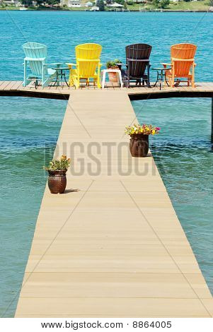 dock with colorful adirondack chairs