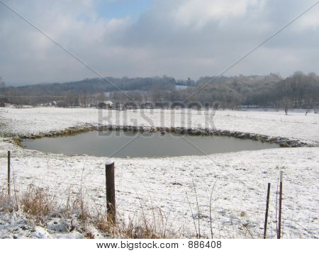 Pond In Snowy Field
