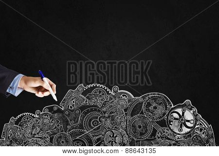 Close up of businessman hand drawing gears on black wall