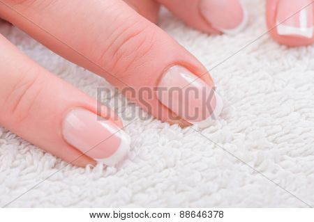 Fingers with french manicure on white towel
