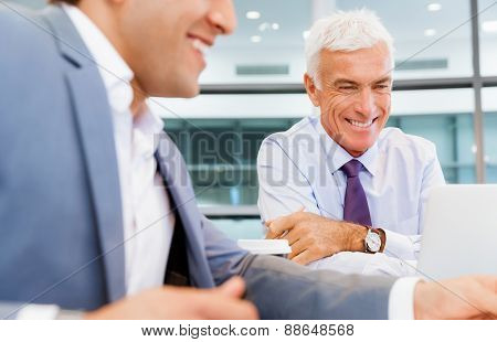 Two businessmen discussing their business in office
