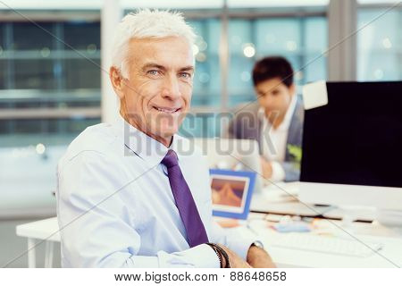 Businessman in office smiling at camera