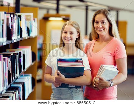 Girl and her mother in library choosing books