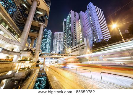 traffic light trails and office buildings in modern city