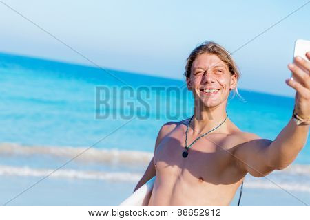 A young surfer taking his selfie on the beach