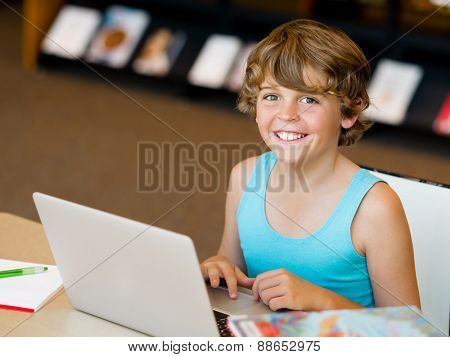 Little boy with laptop in library