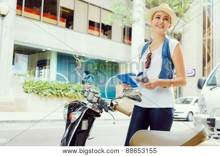 Happy young woman with a map and scooter