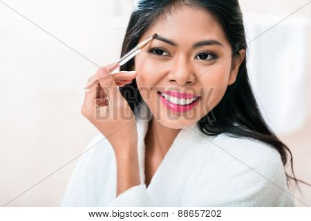 Asian woman in bathroom plucking eyebrows