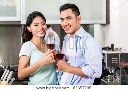 Asian couple, man and woman, drinking red wine in kitchen