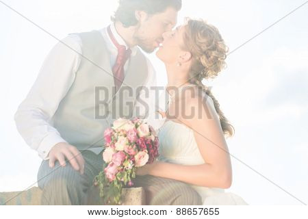 Bridal pair kissing on field after wedding