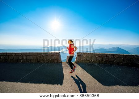 Woman running on the mountain road