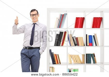 Young man giving a thumb up, leaning on a bookshelf and looking at the camera isolated on white background