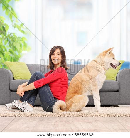 Young woman posing seated beck to back with her pet dog in front of a modern gray sofa at home shot with tilt and shift lens