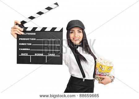 Young female movie director holding a movie clapper board and a box of popcorn isolated on white background