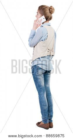 back view of standing young beautiful  woman and using a mobile phone. girl  watching. Rear view people collection.  backside view of person.  Isolated over white background.