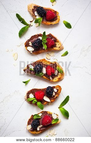 Sweet berry bruschetta with chocolate nut butter,mint and sliced almonds on the white vintage dish
