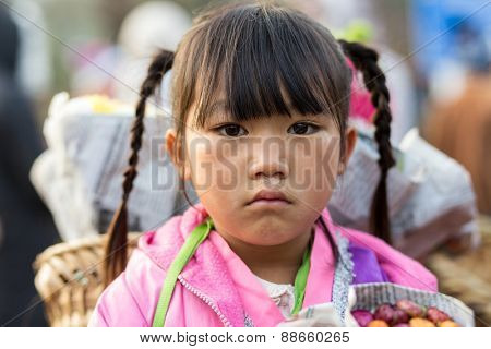 CHIANG MAI, THAILAND, DECEMBER 31, 2014: Portrait of a little Karen tribe girl selling flowers for Buddhist offerings in the Doi Inthanon national park near Chiang Mai, Thailand