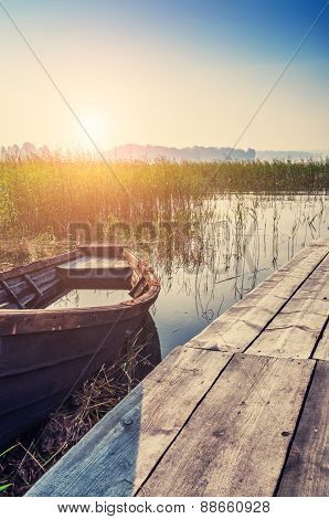 Old Boat On The Coast Of Lake At Sunset