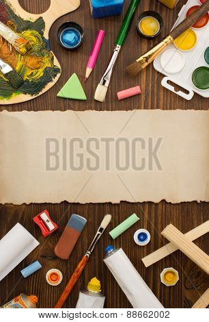 paint supplies and brush on wooden background
