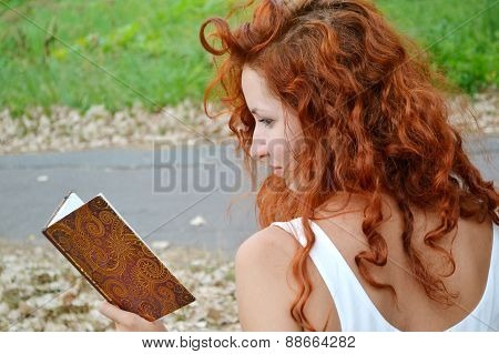 Beautiful redheaded woman with curly hair reading against autumn nature