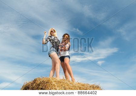 College friends having fun on harvested farm field