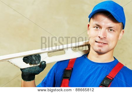 portrait of young plasterer with float over renovation wall backgroung