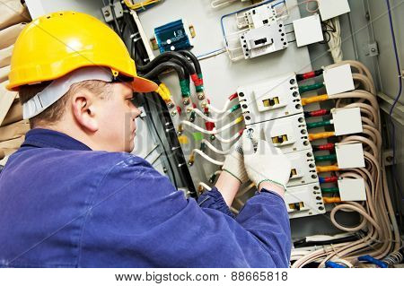 electrician builder at work with tester measuring high voltage and current of power electric line in electical distribution fuseboard