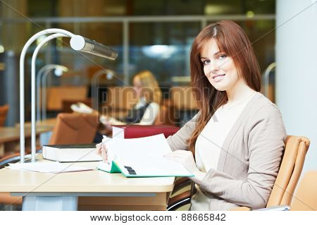 Studying young teenage college student girl  in a library with books